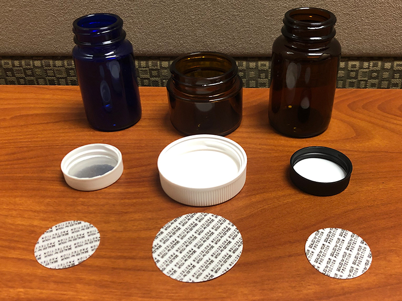 Bottles with pressure sensitive seals and caps off